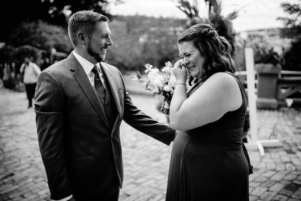 groom comforts crying sister after wedding ceremony
