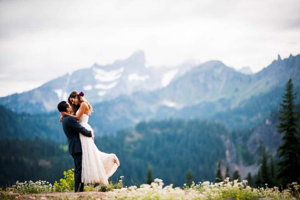 groom picks bride up mountain view