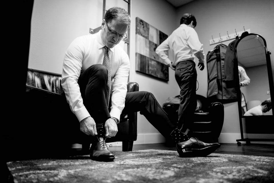 groom tying his shoes as groomsmen gets ready in backgroup