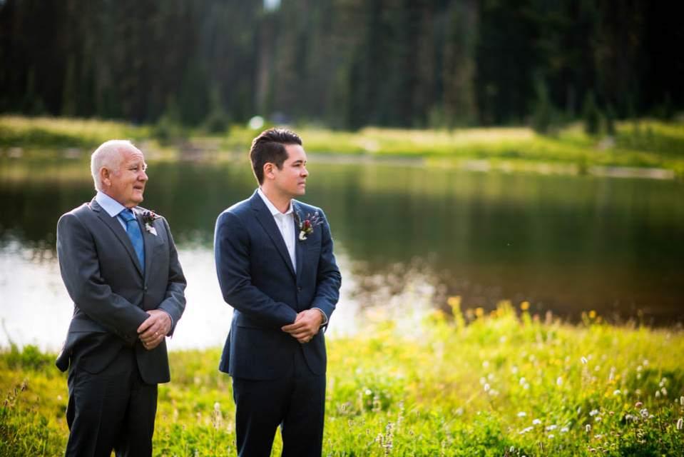 groom waits for bride at alpine lake
