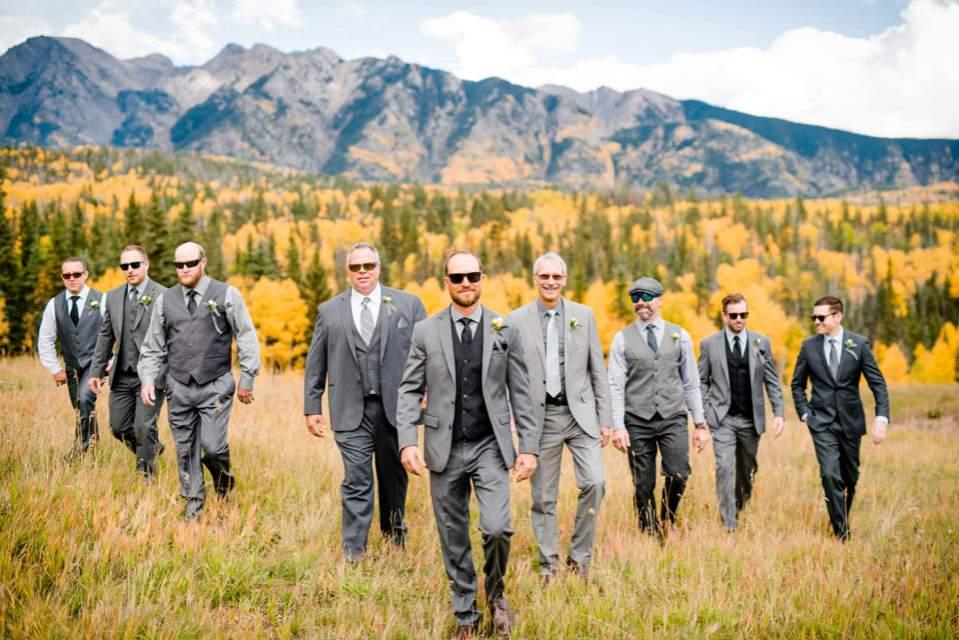 groom with groomsmen walking mountain backdrop
