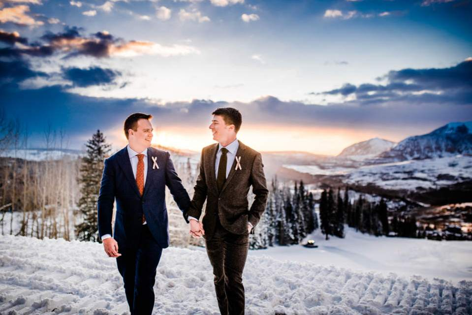 grooms walking together away from sunset at ski lodge in mountains