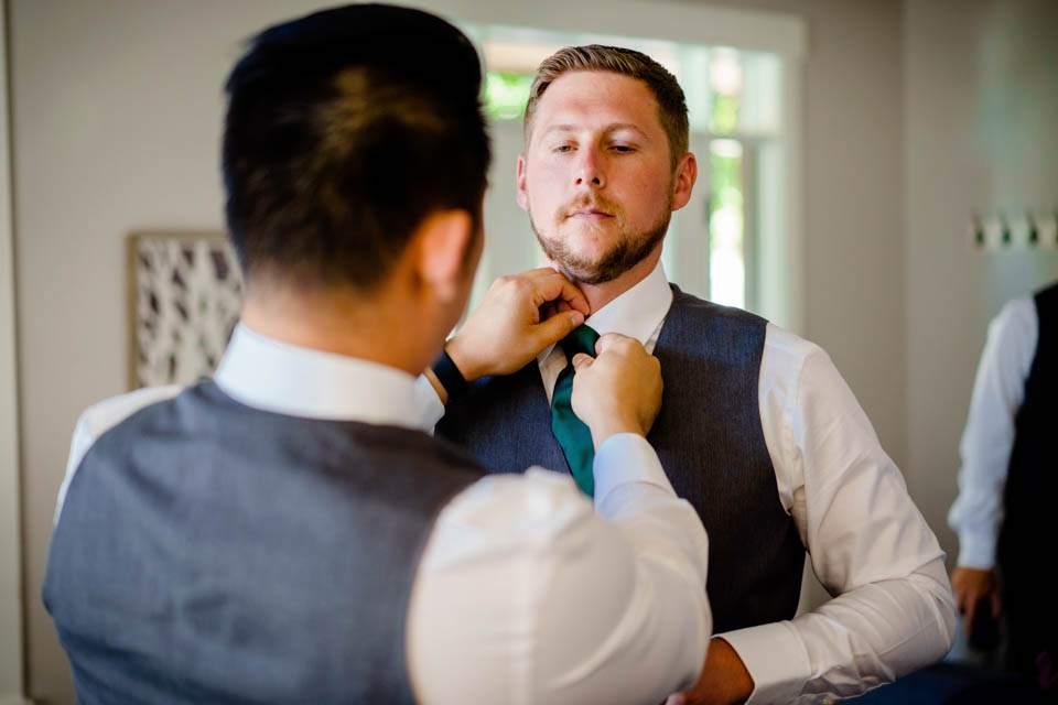 groomsmen helping with grooms tie