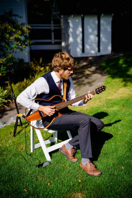 man playing music on guitar for wedding ceremony