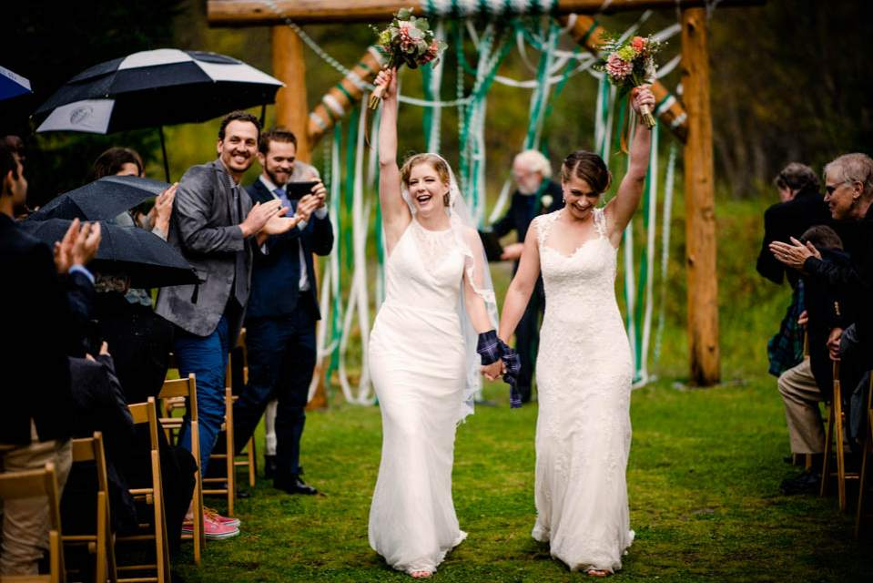 two brides cheering walking down aisle after being married 2