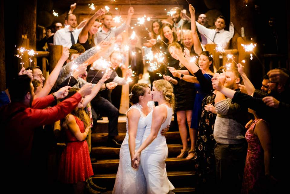 two brides kiss as guests cheer holding sparklers 2