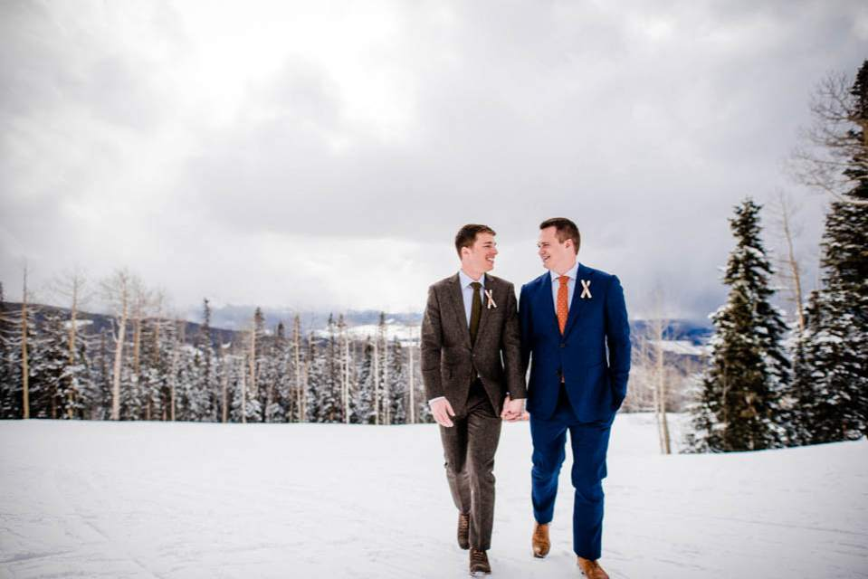 two grooms holding hands and walking