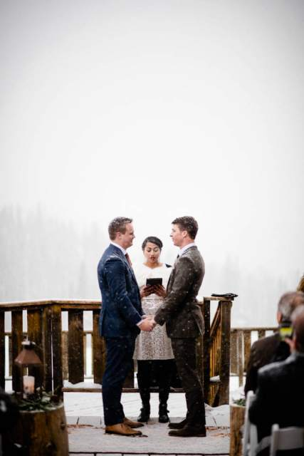 two grooms saying vows to each other